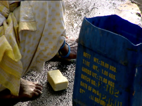 Woman washing clothes on ground Mumbai
