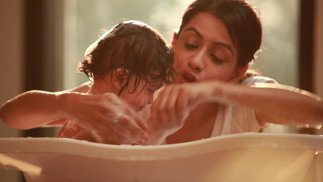 Woman washing her baby in a bathtub