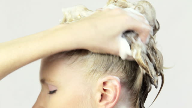 Woman washing her Hair with Shampoo.