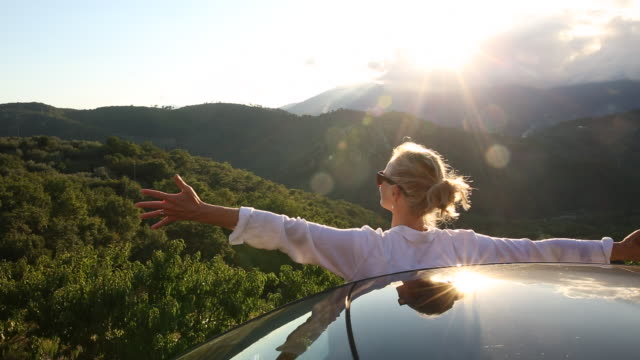 Woman watch sunrise over hills from car, spreads arms wide