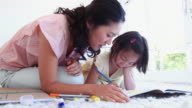 Woman watches a girl as she colours
