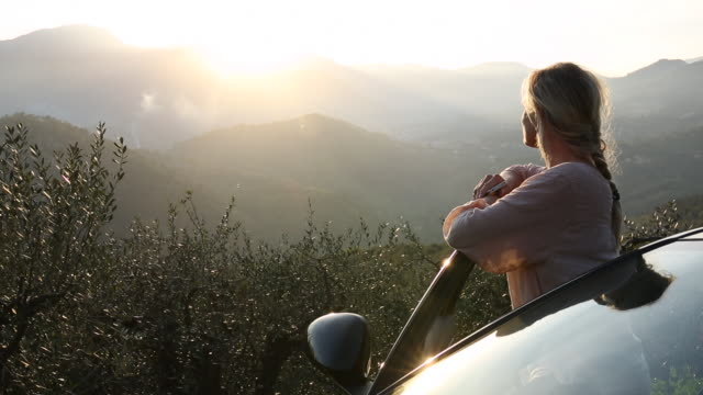 Woman watches sunrise over hills from car door