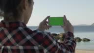 Woman watching smartphone green screen