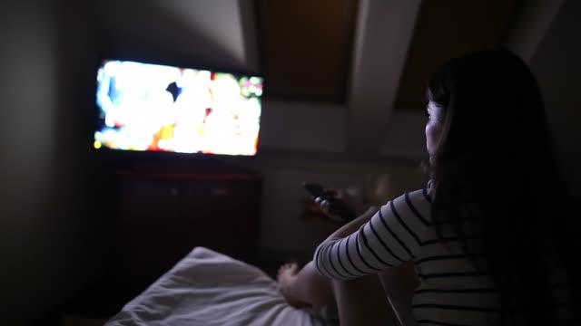 Woman watching TV at night.
