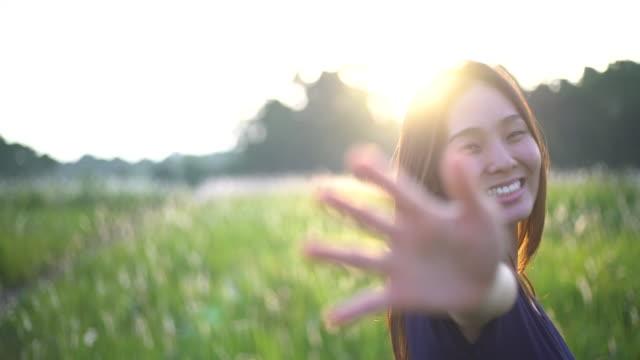 Kvinna viftande hand i fältet, Sunligh