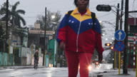 Woman wearing a Venezuelan flag sport uniform walking to work Scenes of the Central Road traversing the city The Central Road was built before the...