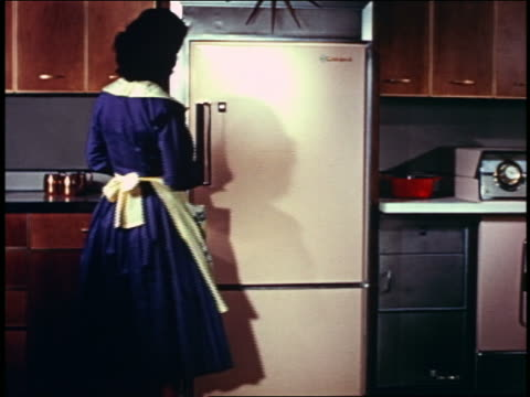 1958 REAR VIEW woman wearing apron opening door of refrigerator in kitchen