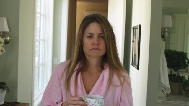 CU Woman wearing bathrobe drinking tea standing in hallway, Phoenix, Arizona, USA