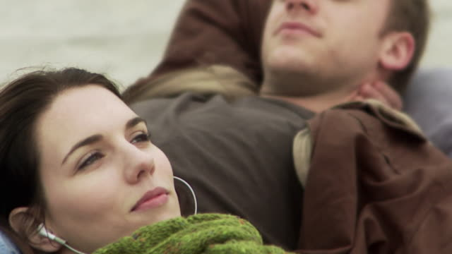 CU SELECTIVE FOCUS Woman wearing ear buds resting on young man's lap on beach / Sea bright, New Jersey, USA