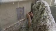 CU Woman wearing headscarf weaving rug on loom / Teheran, Iran