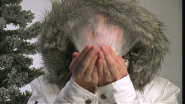 CU, SLO MO, woman wearing hooded jacket blowing snow from cupped hands in studio