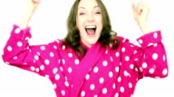 Woman wearing pink spotted bathrobe dressing gown cheering and celebrating.