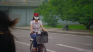 MS PAN Woman wearing pollution mask riding bike down street, Beijing, Beijing, China