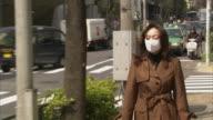 MS ZO Woman wearing pollution mask walking along street, Tokyo, Japan