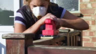 Woman Wearing Protective Mask Uses a Power Sander