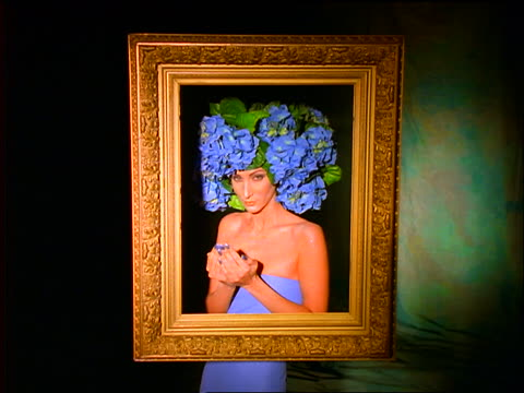 Woman wearing purple/blue flowers on head poses for camera / extends arms thru empty picture frame