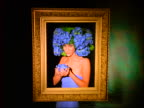 Woman wearing purple/blue flowers on head throws flower petals through empty picture frame