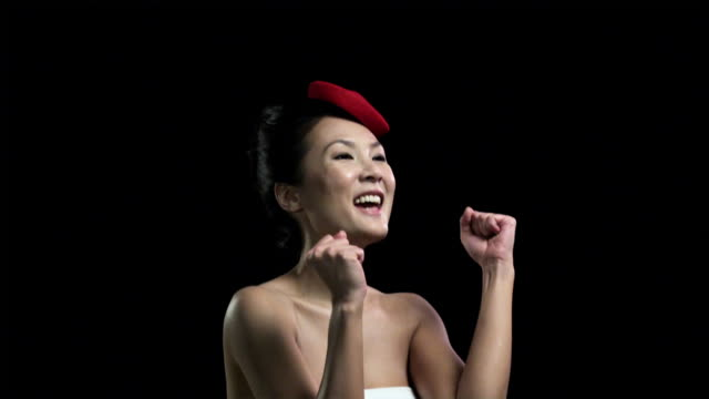 Woman wearing red hat clapping and cheering