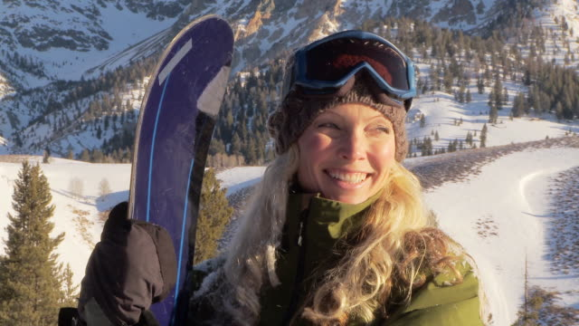 Woman wearing snow gear poses with snowboard / Blaine County, Idaho, United States