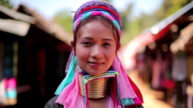 woman wearing the traditional metal rings around her neck,working at a weaving in village
