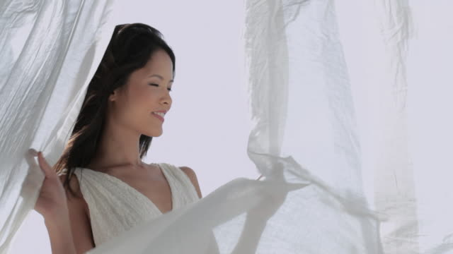 MS TU Woman wearing white dress and hair blowing in wind / Singapore