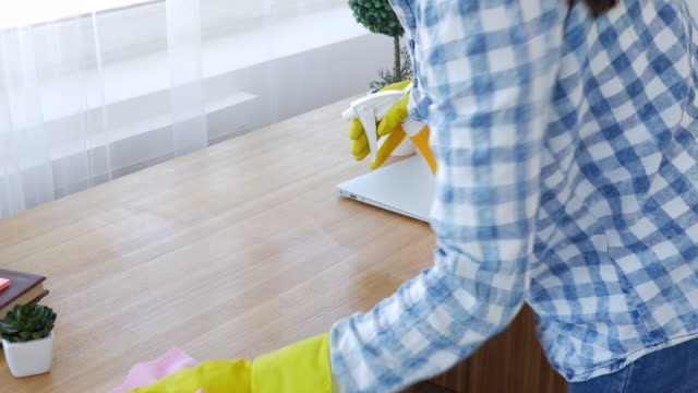 Woman wearing yellow gloves and dusting desktop