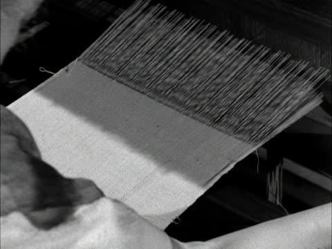 A woman weaves fabric on a handloom