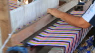 Woman weaving cotton on a loom in Thailand