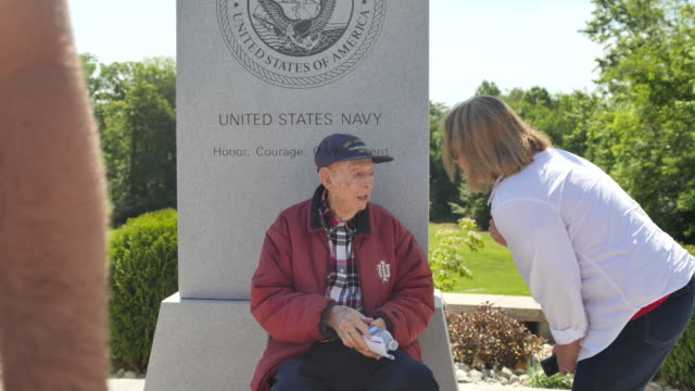 A woman whose father served in the Navy talks to a WWII Navy vet during Memorial Day ceremonies at Valhalla Memory Gardens May 29 2017 in Bloomington...