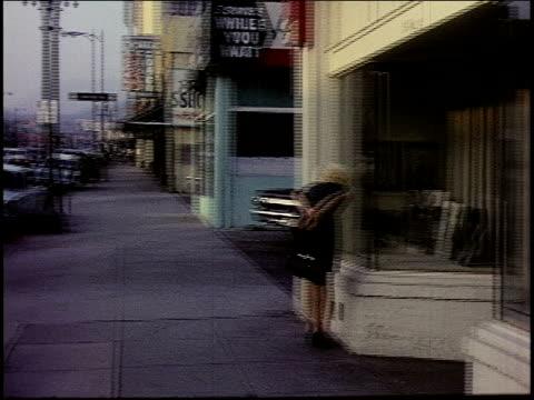 Woman window shopping / woman hitchhiking