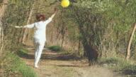 SLO-MO-Frau mit einem Ballon mit ihrem Hund im Wald laufen