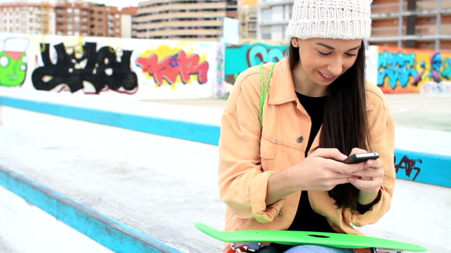 Woman with a Skateboard texting on her phone