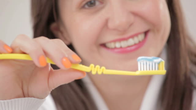 Woman with beautiful smile holding a tooth brush