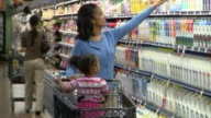 MS Woman with daughter (2-3) sitting in shopping trolley choosing yoghurt in supermarket, Richmond,  Virginia, USA