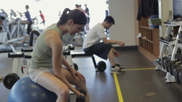 MS DS Woman with dumbbells exercising in gym / Vancouver, British Columbia, Canada