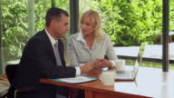 MS Woman with financial advisor looking documents on laptop / Eastbourne, Sussex, UK