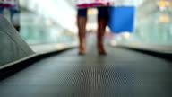 Woman with fridge bag on Moving walkway