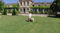 WS, Woman with Golden retriever walking on lawn in front of palace, Saint Ferme, Gironde, France