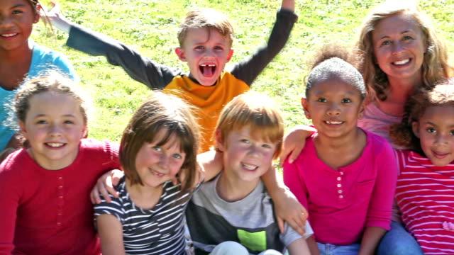 Vrouw met groep kinderen zitten op gras