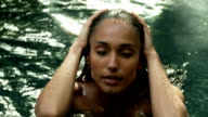 Woman with hands on her face in a natural pool