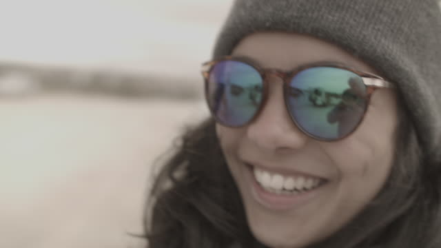 Woman with hat smiling into camera with photographer reflected in sunglasses