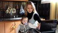 Woman with laptop and baby in a kitchen