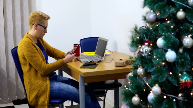 Woman with laptop computer and christmas tree