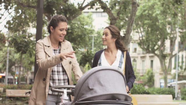 Woman with pregnant friend and baby carriage