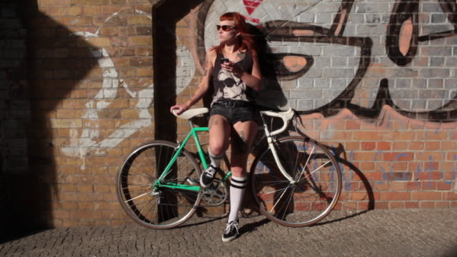Woman with red hair and bike leaning against graffiti wall texting.