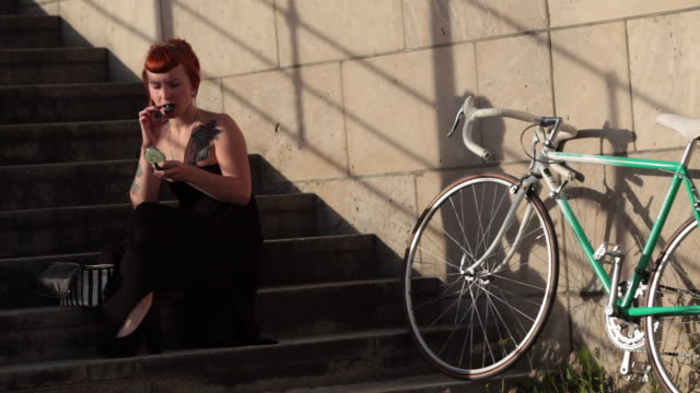Woman with red hair and tattoos fixing her make up on stone steps in evening sun in Berlin, Germany.