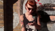 Woman with red hair enjoying sun and looking at mobile phone in Berlin, Germany.