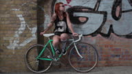 Woman with red hair sitting on bike leaning against graffiti wall, smoking.