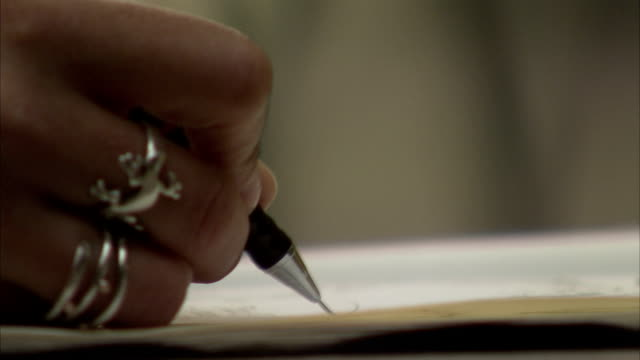 A woman with silver rings on her fingers writes with a pen on paper. Available in HD.