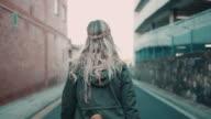 Donna con skateboard a piedi sulla strada